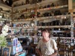 Sales lady in shop with money from all around the world